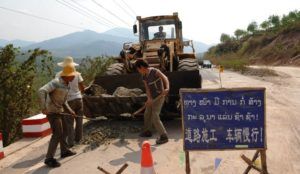 To go with AFP story 'Laos-economy-invest-China,FEATURE' by Amelie Bottollier-Depois Photo taken March 11, 2011 shows Chinese workers repairing a road leading to the border town of Boten, a special economic zone land hired by China, in the Northern province of Luang Namtha. Recently still dependent on foreign development aid, Laos is benefitting from massive investments from its vietnamese and chinese neighbours.  AFP PHOTO / HOANG DINH Nam